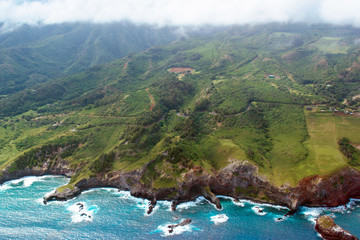 Aerial view of Maui's coastline shows everything from Pacific surf to mountains and clouds, shot from a small, low-flying prop plane