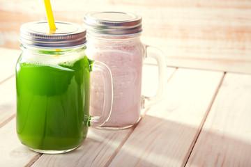 Green healthy smoothie in glass jar on rustik wood