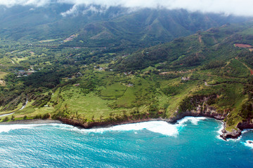Aerial view of Maui's coastline shows everything from Pacific surf to green fields to mountains and clouds, shot from a small, low-flying prop plane