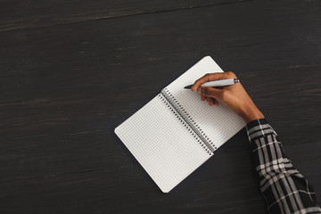 Black woman writing in notebook, top view