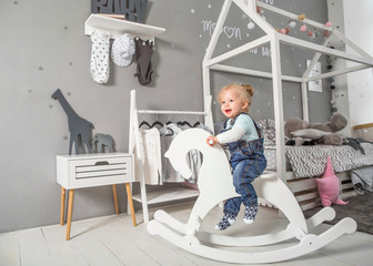 one year old girl playing near in the room with a toy horse, skating