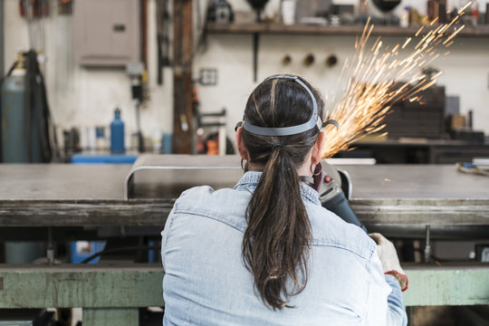 Rear view of woman wearing safety glasses and dust mask standing in metal workshop, using power grinder, sparks flying.