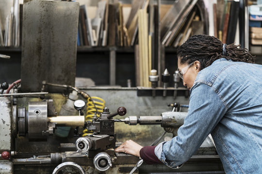 Woman wearing safety glasses standing in a metal workshop, working at a machine.