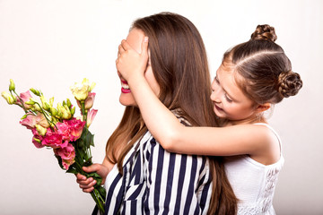 daughter gives her mother flowers in the studio, happy mother's day