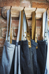 Denim work aprons hanging on a row of hooks on a brick wall.