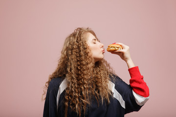 Beautiful young girl kiss burger curly hair on pink background. Concept love of fast food - burgers.