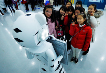 Girls pose for a photograph taken by a robot at the Gangneung ice hockey arena at the PyeongChang 2018 Winter Olympics in Gangneung