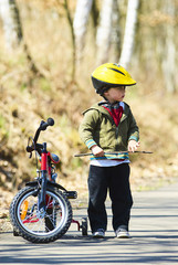 Little boy on bicycle in green park outdoor in summer. A child is riding a children's bike with support wheels  wearing safety helmet