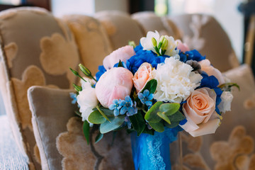 Bridal bouquet with creamy roses and peonies and blue hydrangeas. Wedding morning. Close-up