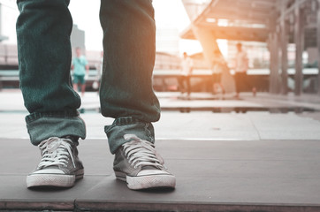 close up legs men casual wearing jeans and shoes stand on concrete stair. waiting, start  up and ready concept. travel concept.