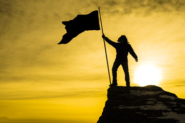 silhouette of man on top of mountain with victory flag, background sky with rays of sunset sunset. Business concept idea
