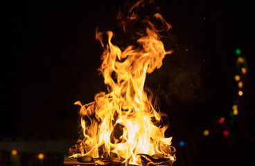 Fire with flames and bokeh lights. Big blaze on black blurred background. Close up view with details, space for text.