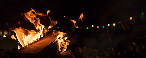 Fire with flames and bokeh lights. Bonfire with blurred people on night background. Close up,details, banner, space for text.