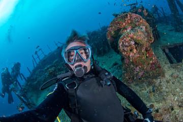 Wall Mural - Scuba diver smiling underwater selfie portrait in the ocean