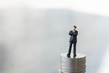 Business and Money Concept. Businessman miniature figure standing on top of stack of silver coins.