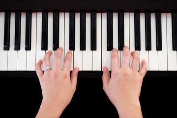 Woman playing piano. Top view with black isolate background. Art and music background.