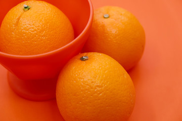 Orange fruit staged with simple color background.  Shows trio of the fresh citrus fruit for organic produce within the food industry.