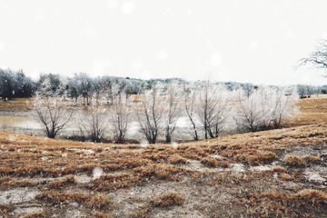 Rural farm pasture wet from snow and ice during winter gray day.  Frost makes landscape look cold and frozen.