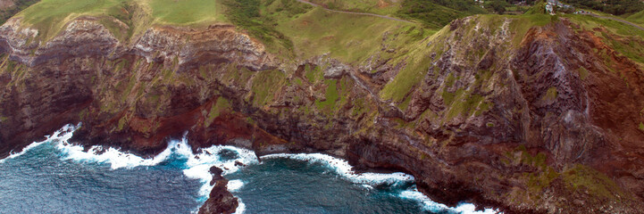 Aerial panorama of Maui's rocky coastline, shot from a small, low-flying prop plane