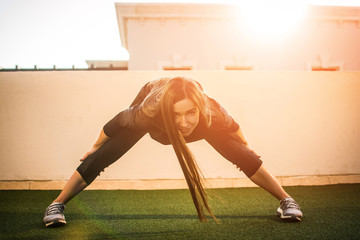 Fit girl in sportswear exercising at rooftop outdoors during sunset.