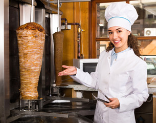 Female chef cutting meat for shawarma .