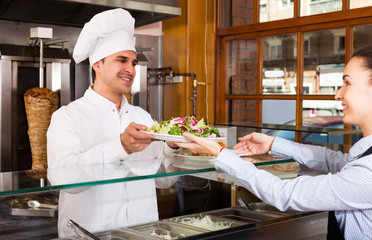 Ordinary waitress receiving order from chef