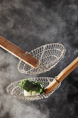 Bok choi in metal strainer with  steam rising