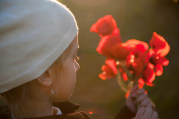 little girl wearing hat holding bouquet of poppy flowers in spring sunset