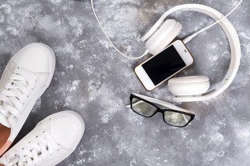 Flat lay Of White Sneakers On stone Background with phone and headphones.