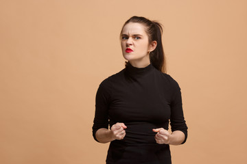 Portrait of an angry woman looking at camera isolated on a pastel background