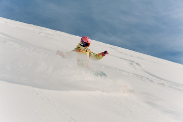 Female snowboarder in colorful sportswear and pink helmet riding down the powder snow hill