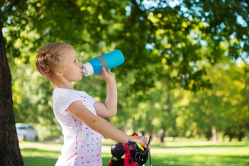 Pretty girl with bicycle drinks water in summer park