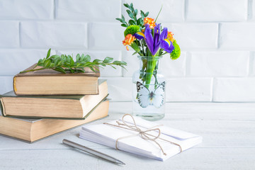 Old books and envelopes, a vase of flowers against a white brick wall.
