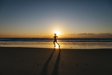 Woman jogging on beach at sunrise, Noosa Heads, Queensland, Australia