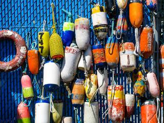 A group of brightly colored fishing buoys hangs on display at Charleston Harbor near Coos Bay, Oregon, USA