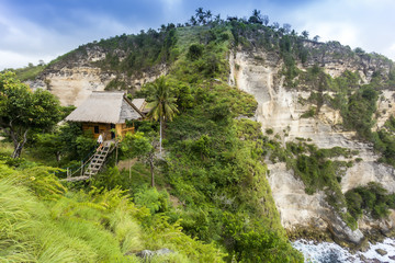 Woman outside thatched roof hut on coast with cliffs, Nusa Penida, Bali, Indonesia
