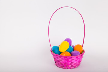 Easter egg basket with brightly colored plastic easter eggs on white background