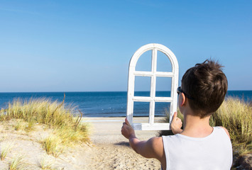 Wall Mural - Traum vom Haus am Strand - Junge blickt durch ein Fenster auf das Meer