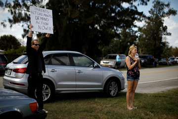 Melissa Conrad-Freed, former student at Marjory Stoneman Douglas High School, mourns while she holds pictures of Aaron Feis, one of the victims of the mass shooting at that school, close to the fence of Western High School during a protest in support of th