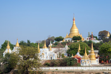 View of many golden stupas in Sagaing near Mandalay in Myanmar (Burma) on a sunny day. Copy space.