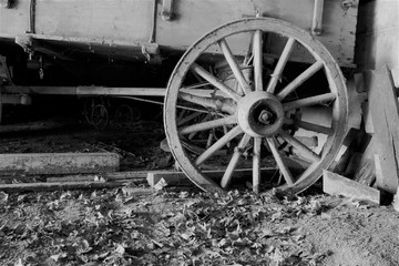 Old wagon wheel on a cart with a dirt floor in black and white