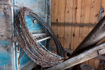 Rusty barbed wire leaning on an old, blue painted wagon. Barn scene with a loop of barbwire and an antique wagon. Concepts of farming, ranching, western, tourism, vintage