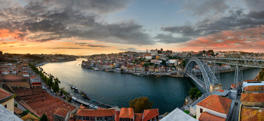 Porto, Portugal panoramic cityscape on the Douro River and Dom Luis I Bridge at sunset. Urban landscape at sunset with traditional boats of Oporto city.