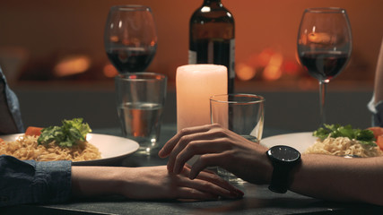 Man touches woman's hand during a romantic date. Close-up