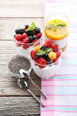 Chia pudding with berries in glasses on grey wooden table
