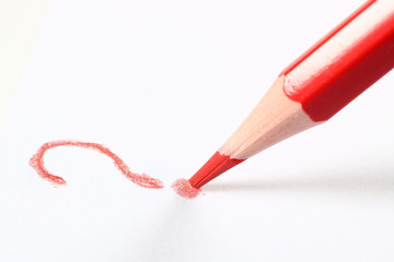 A red pencil writes a white background question mark on a white background