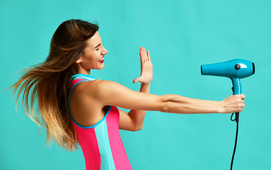 Happy young brunette woman pointing hair dryer on blue mint