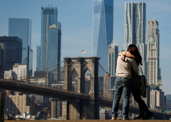 A couple embrace with the Brooklyn Bridge and lower Manhattan skyline in the distance during unseasonably warm weather in Brooklyn, New York
