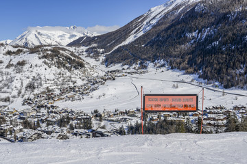 Signpost written in various languages warning of expert ski run ahead. View of Thuile town in valley below Valle d'Aosta, Italy