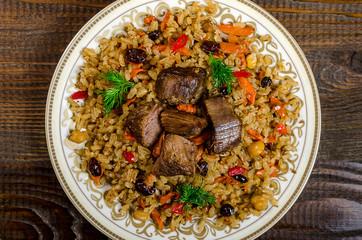 Uzbek national pilaf dish on a dark wooden background